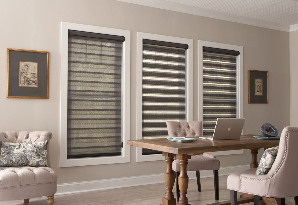 three large dark gray Allure® Transitional Shades on a beige wall behind a table with a laptop on it