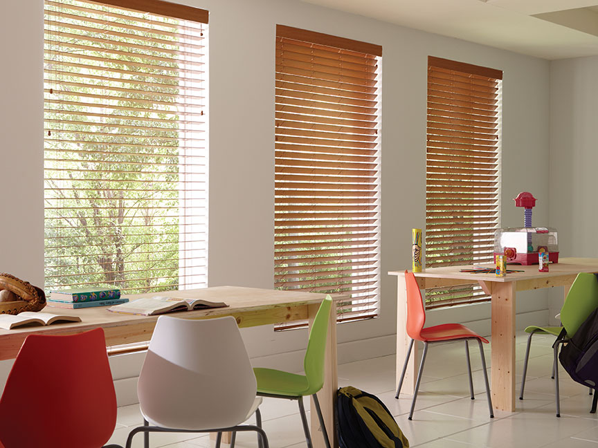 Three large custom stained faux wood blinds hang in a classroom with brightly colored chairs.