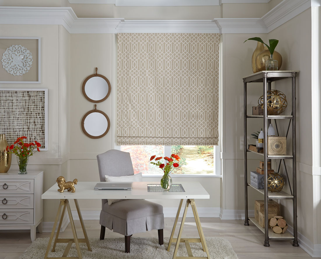 patterned tan Interior Masterpieces® fabric shade in a window behind a desk with a gray chair and laptop