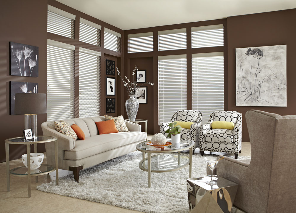 Several white Heartland Woods® Wood Blinds & Interior Masterpieces® Custom Pillows on a white couch and chairs with circular geometric patterns