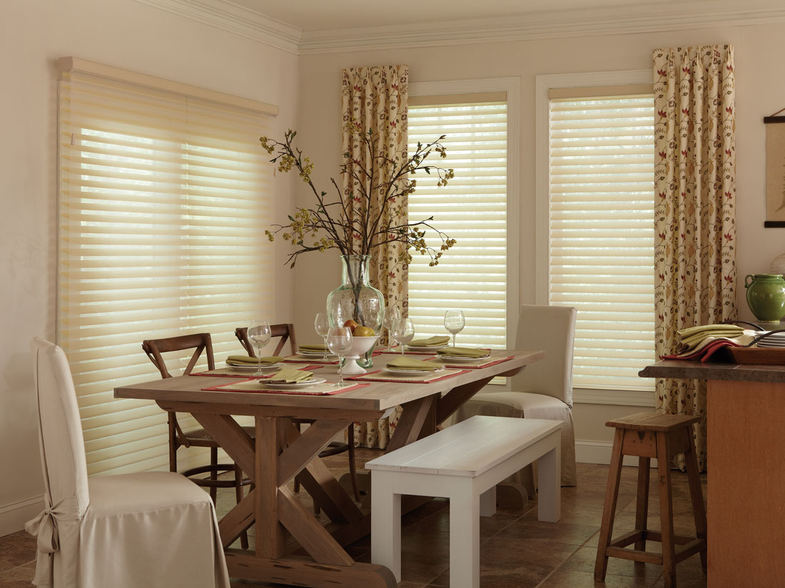 Light tan colored Tenera® sheer shades hanging over a wide patio door on one wall and two windows on the other wall with Interior Masterpieces® Draperies accenting them along with a dining room table that has Interior Masterpieces® table accessories on it