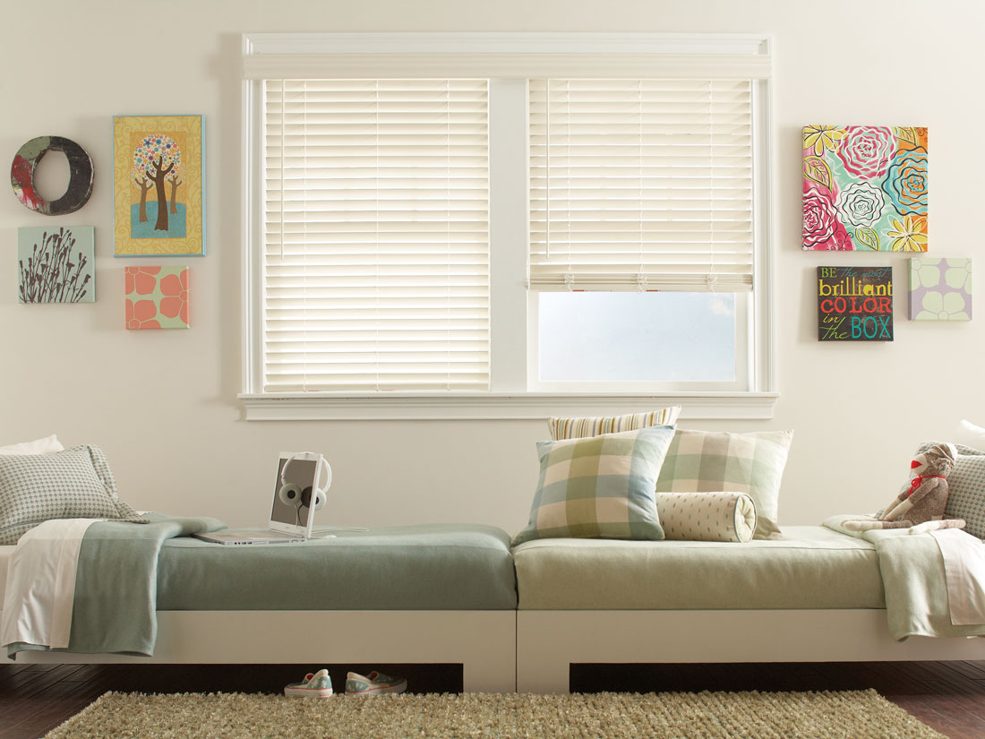 White Fidelis® Faux Wood Blinds in a bedroom with two beds in front that have light green Interior Masterpieces® Bedding and Pillows