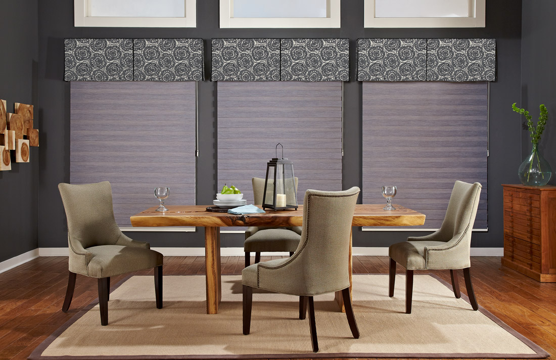 three large gray Allure® Transitional Shades with green and blue floral patterned Interior Masterpieces® fabric cornices against a dark gray wall behind a brown table and chairs