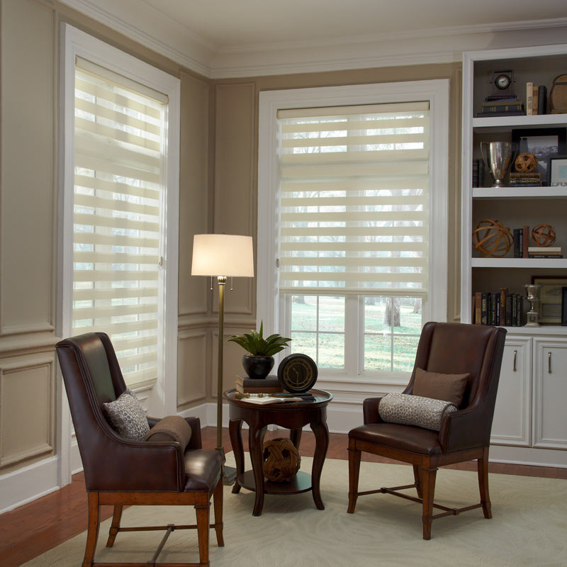 two cream colored Allure® Transitional Shades on a room behind a small dark desk with matching chairs
