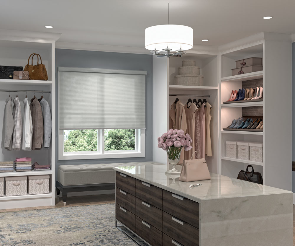 large gray Genesis® Cassette Roller Shade in a closet next to clothes and a dresser in the foreground with pink flowers on it