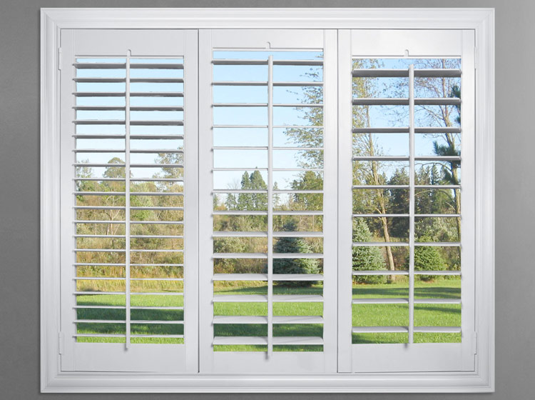 Three white Parke® Shutters panels with different sized louvers looking out to a green yard and tree line set against a dark gray wall