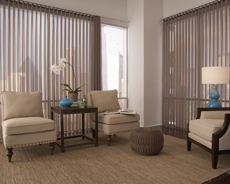 Warm gray sheer fabric wrapped vertical blinds hang in a sitting room area in a sky rise apartment with dark features, tan chairs and a brown rug.