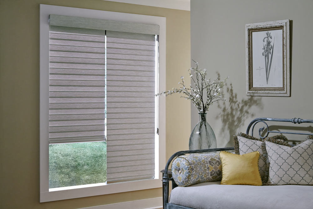 two light gray Allure® Transitional Shades under one cassette in a large window against cream colored walls witha bench that has Interior Masterpieces® Custom Pillows in yellow and a floral pattern on it