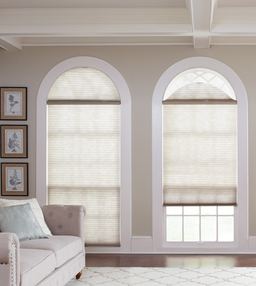 Custom Cellular shades adorn two arched windows, one with shades closed one with shades open showing the separately operable shade covering the arch.