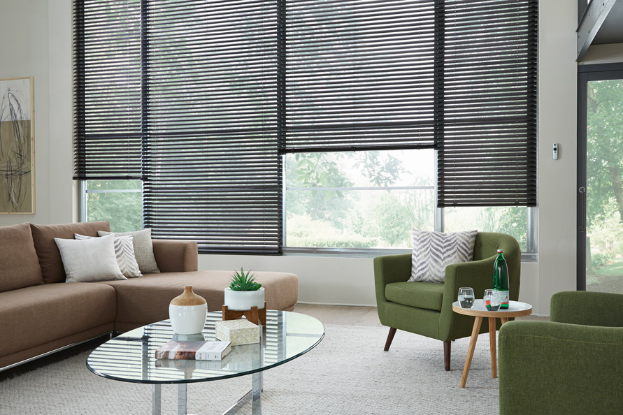 """4 large windows with black 2"""" aluminum blinds behind a modern sofa and chair with a motorized remote hanging on the wall next to the very large blinds"""