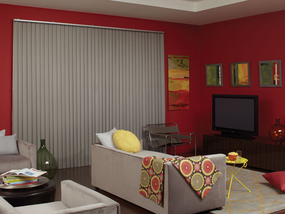 Gray Sheer Visions® Vertical Blinds in a large window in a room with red walls and a light gray couch