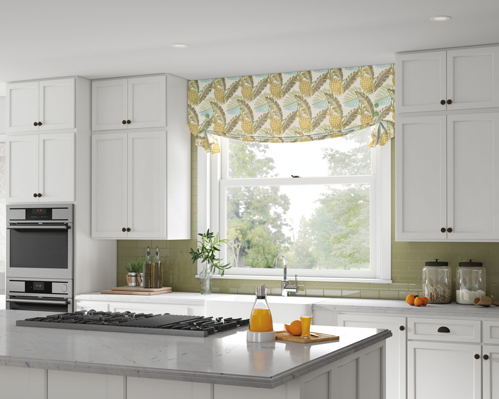 a kitchen with white cabinets and a window behind a sink with a yellow and light blue Interior Masterpieces® Fabric Valance that has pineapple a pattern on it behind a sink