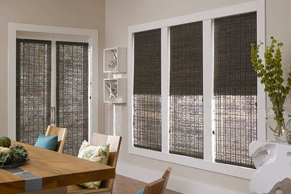 Three dark brown woven wood shades hang in three windows to show the difference in opacity of unlined, lightly lined, and room darkening lined shades.