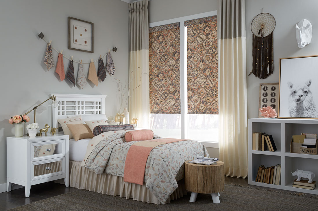 Geometric floral patterned orange and brown Interior Masterpieces® fabric shades with gray and tan draperies hanging on each side with custom bedding on the bed in front