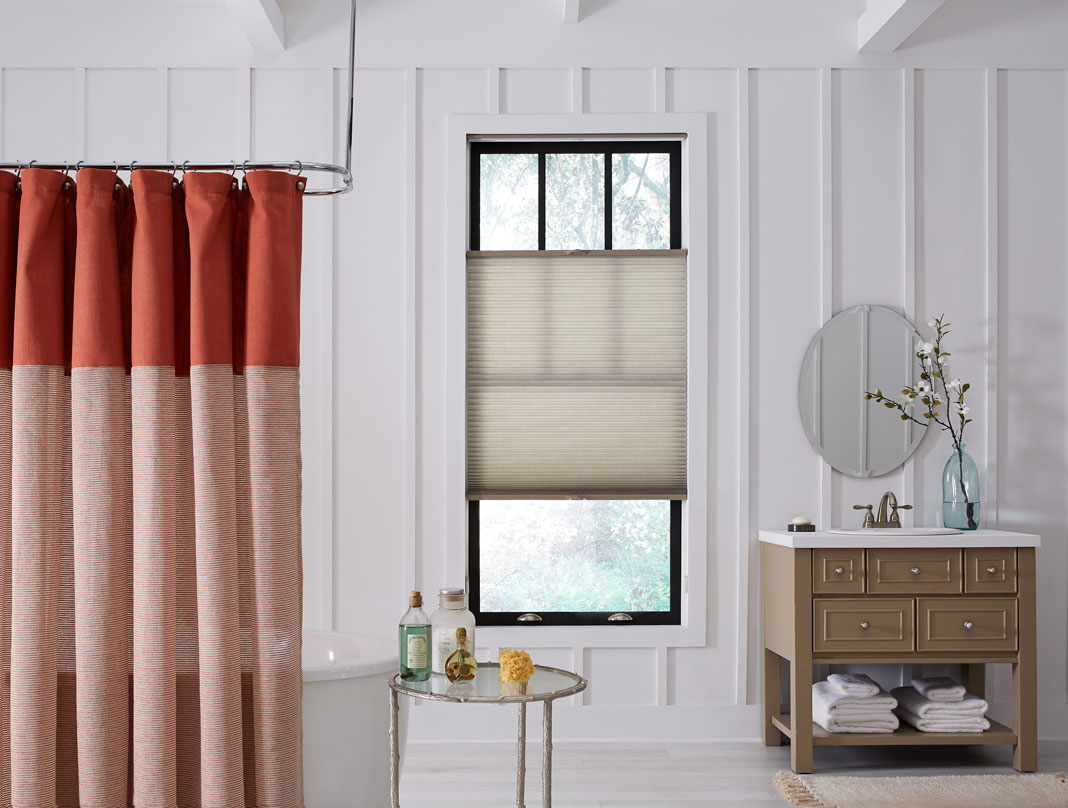 tan Parasol® Cellular Shades in a bathroom with a red shower curtain and brown vanity