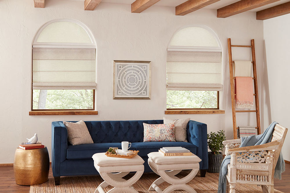 Tan colored Genesis® Hobbled Roman Shades with half circle Custom Shapes and a Palladian Shelf between behind a blue couch with tan pillows
