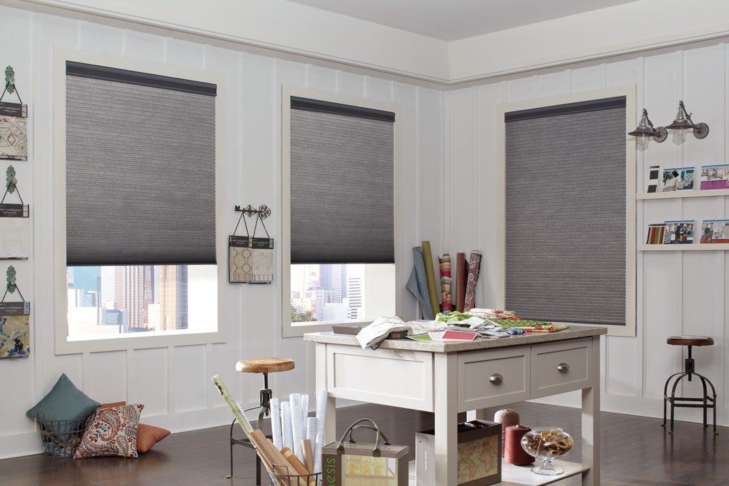3 Parasol® Duo-Lucent Cellular Shades with dark materian in a room with lightly colored walls and desk