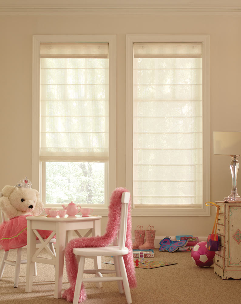 two light tan Genesis® Cordless Roller Shades in a child's room with a stuffed teddy bear at a table with a pink tea set
