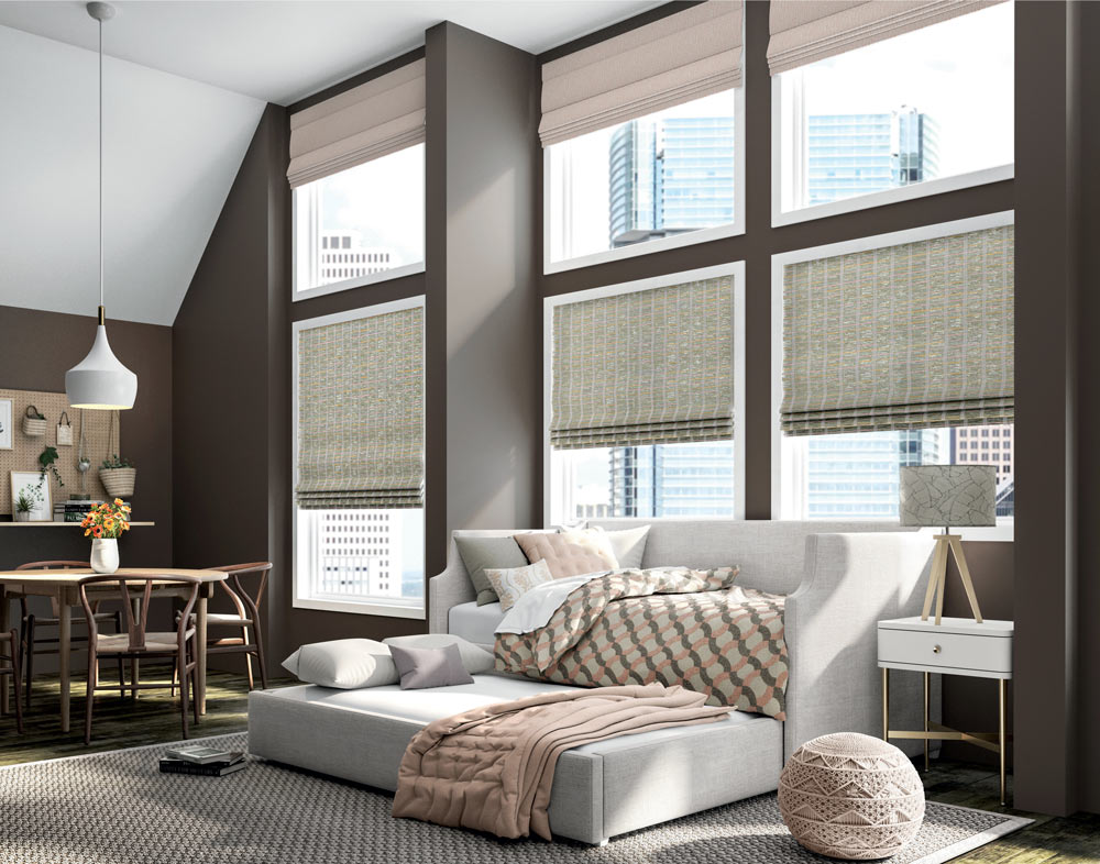 light green Motorized Manh Truc® Woven Wood Shades & pale pink Interior Masterpieces® Fabric Shades against brown walls behind a couch and pull out sleeper with Custom Bedding in pale pink, green, and brown