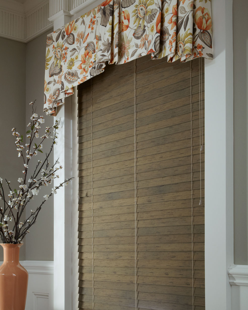 Dark brown Heartland Woods® Wood Blind & Interior Masterpieces Fabric Valance in a white, tan, and orange floral pattern