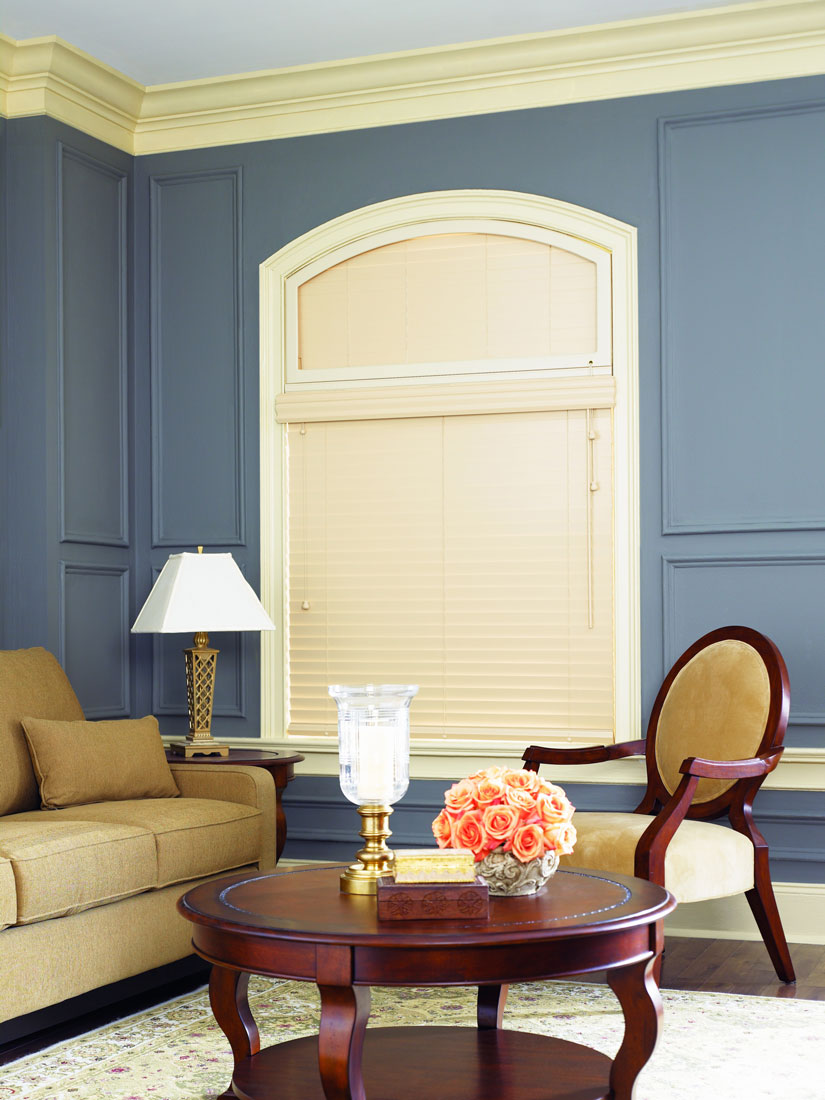 a cream colored Heartland Woods® Wood Blind with a specialty curved top shape above against a blue wall with a tan couch and mahogany table and chair in front