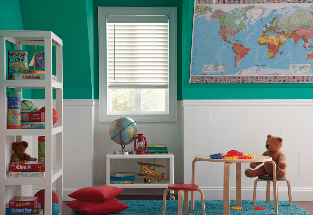 white Heartland Woods® wood blind against a turquoise and white wall with various playthings and a globe in the foreground