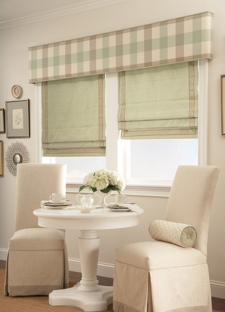 windows with Green Interior Masterpieces® Hobbled Roman Fabric Shades with light brown trim and a tan, brown and green striped Custom Cornice spanning the width of both windows