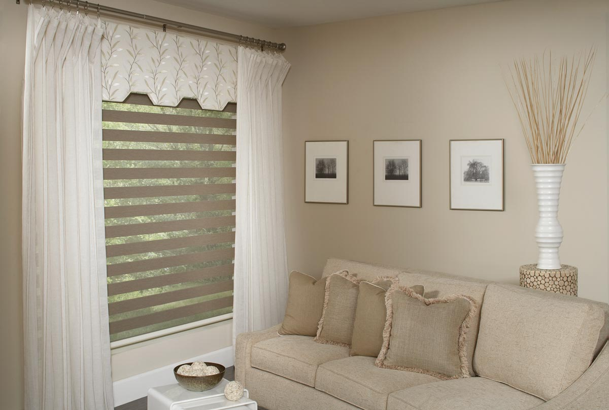 Tan room with white Interior Masterpieces® draperies hanging around a custom Fabric Wrapped Cornice and an Allure® transitional shade