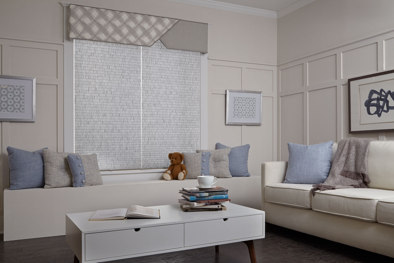 Two Parasol® Cellular shades with the Accu-Rise lifting system in a child's room behind a teddy bear and bench with a Custom Cornice hanging over both shades