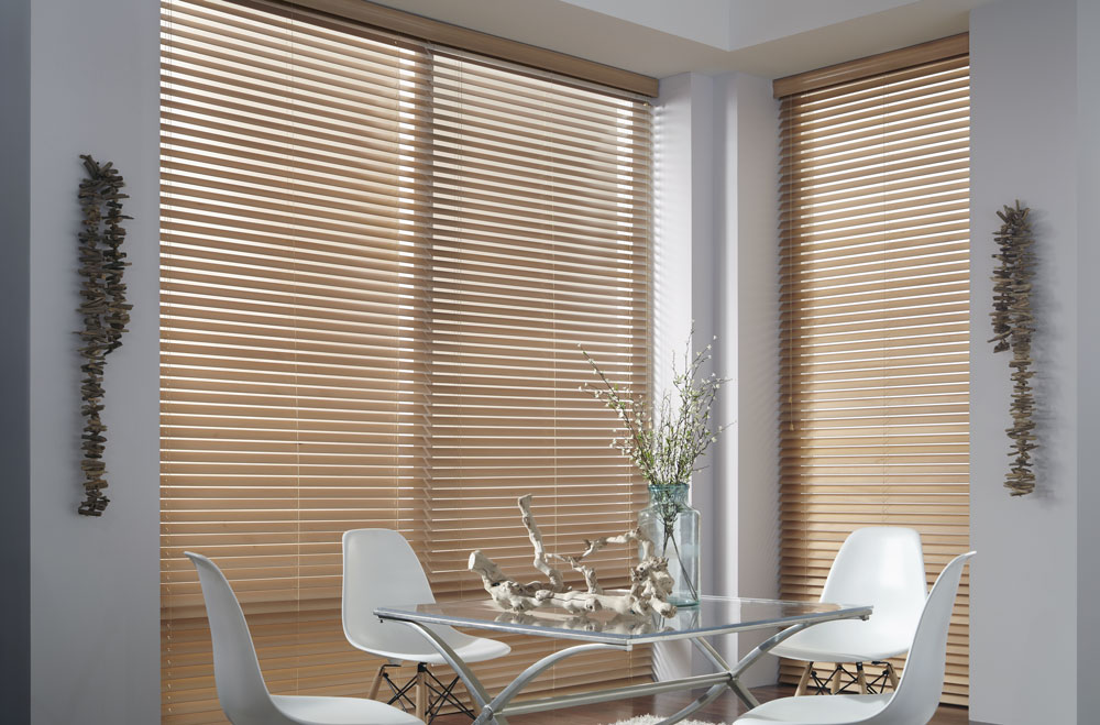 Large brown Heartland Woods® Wood Blinds in a dining room with a clear table and white chairs