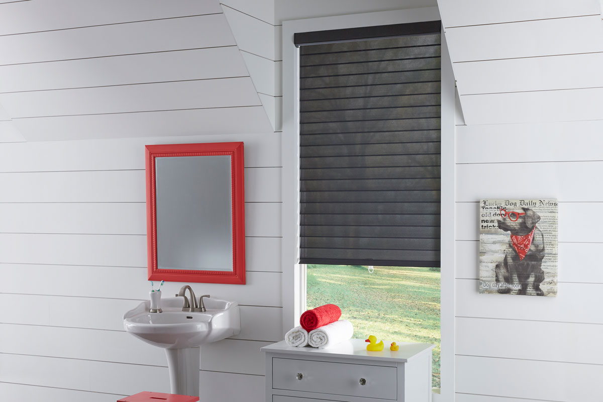 A black Tenera® Sheer Shade with vanes open in a white bathroom with a sink and red mirror next to it