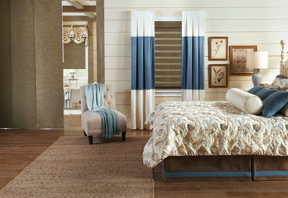brown Allure® Transitional Shade in a window with blue and white Draperies from Interior Masterpieces® along with a Genesis® Companion Roller Shade wtih fabric valance behind a brown Panel Track with a bed that has custom bedding and pillows on it in the