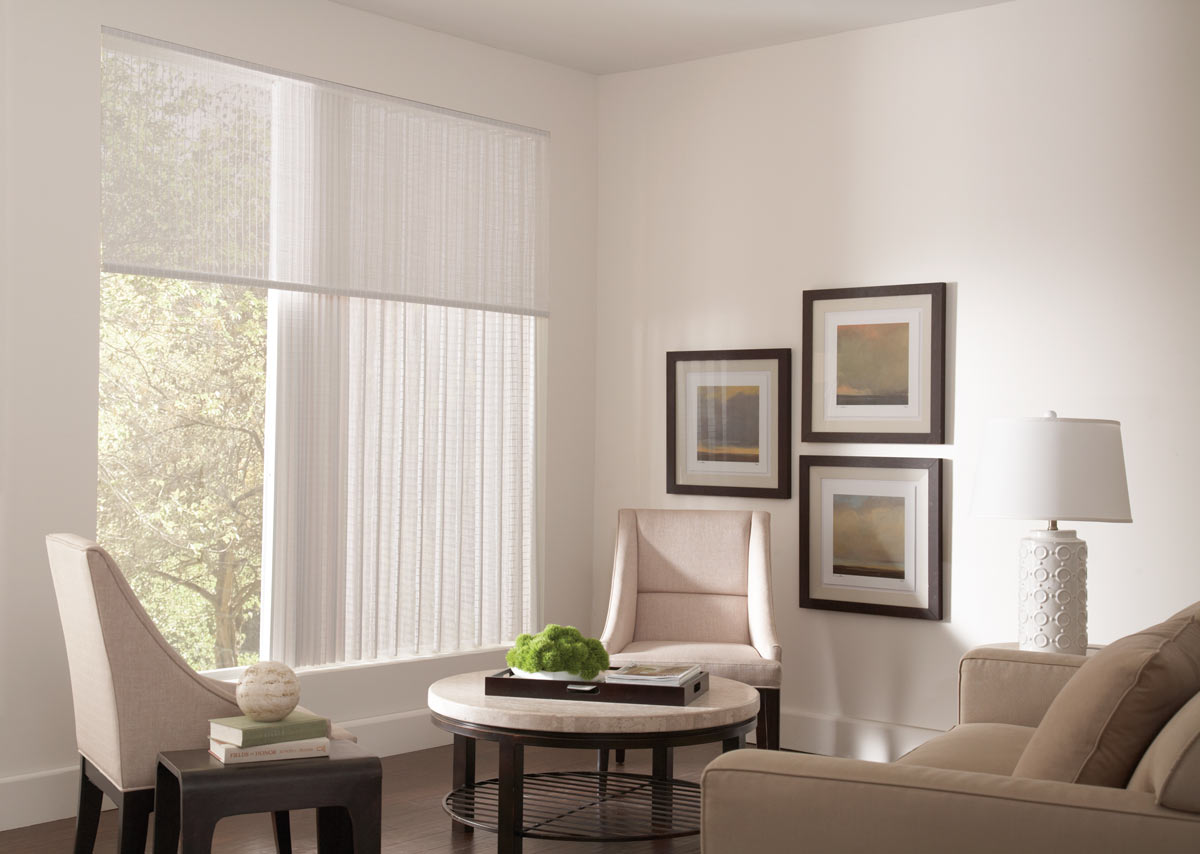 A large, closed white Manh Truc® Woven Wood Panel Drape in a picture window with a Valance in the same material next to a tan table and chairs