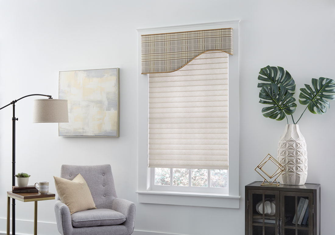 Light brown Tenera® Sheer Shade with light brown plaid Interior Masterpieces® Fabric Wrapped Cornice in a white room with a chair that has a custom Interior Masterpiece® pillow