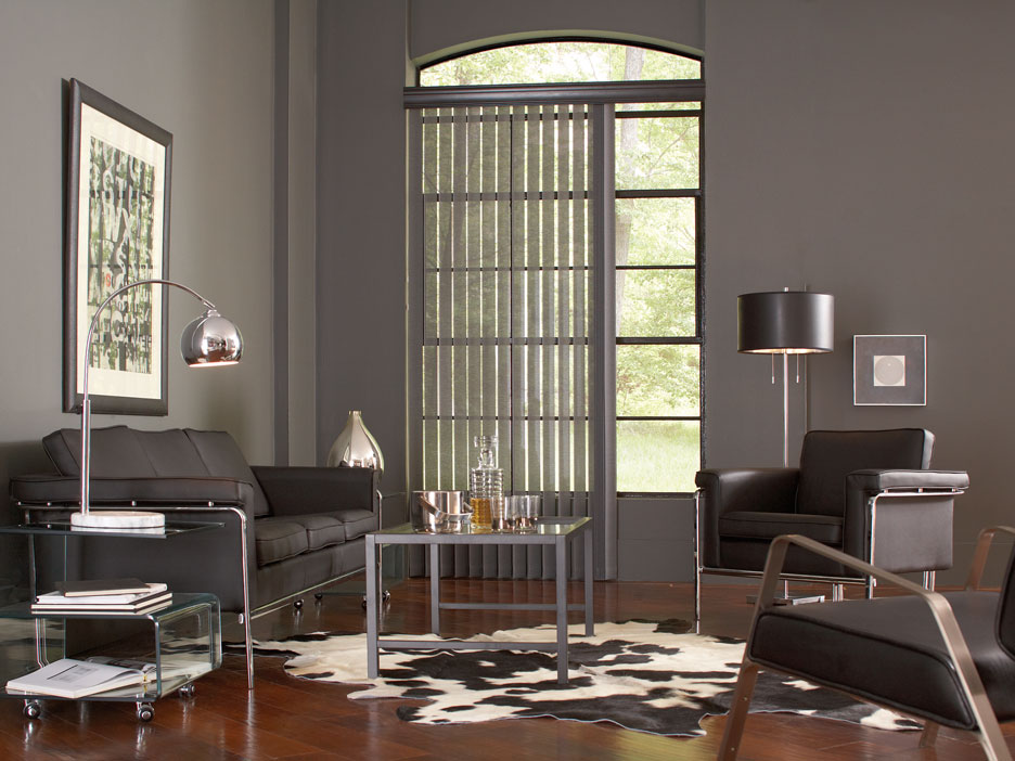 Gray Discoveries® vertical blinds hanging in a window in a room with gray walls and black furniture