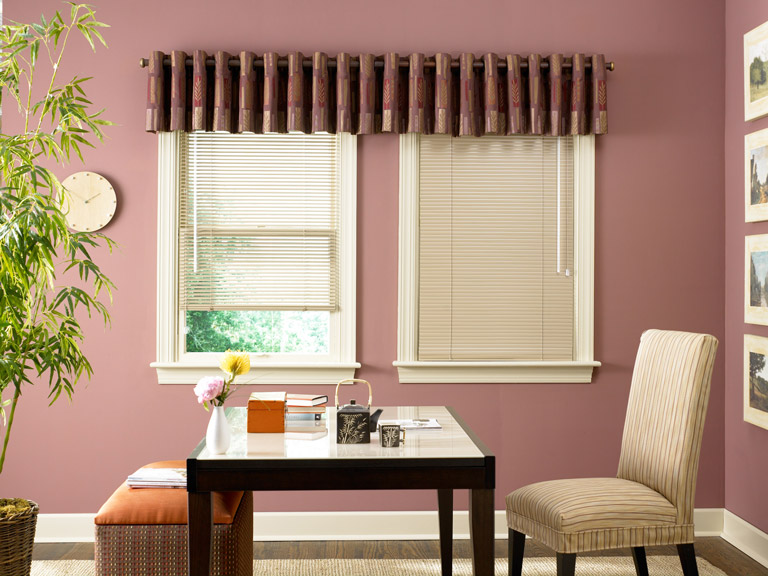 Two tan colored Classic Collection® Aluminum Blinds with a red Interior Masterpeices® Fabric Valance with custom hardware behind a black table and tan chair