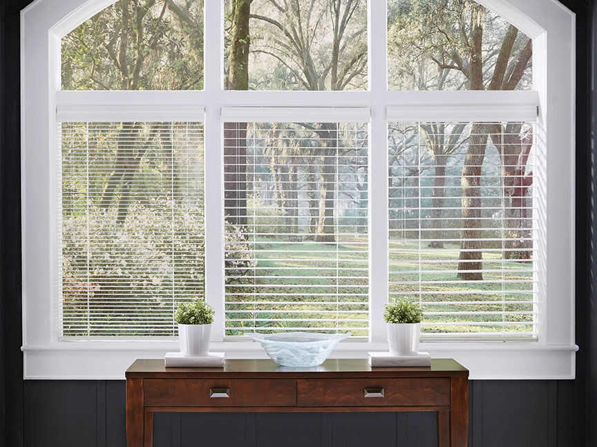 Three custom white wood blinds in three slat sizes, tilted open, hang in an arched window