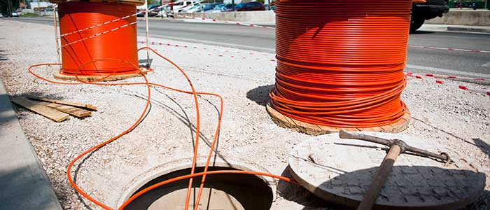 Fiber-optic cables are placed in a hole in preparation for an upcoming internet