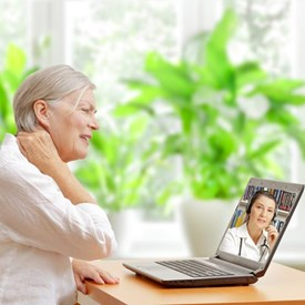Woman describes neck pain to doctor using telemedicine