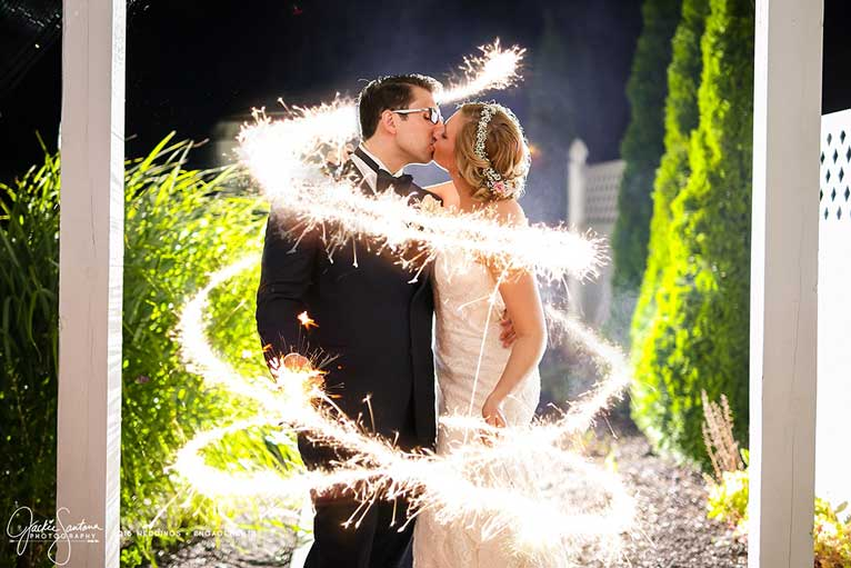 Bride and groom embrace for a photo using sparklers and slow shutter speed in The Lakefront Gardens in Indianapolis