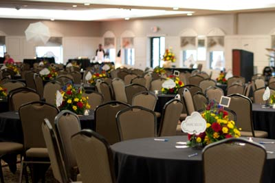Corporate event held in The Ballroom at The Willows featuring petite colorful centerpieces