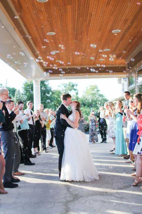 Bride and Groom kissing in front of The Ballroom at The Willows at their wedding reception