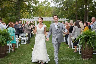 Mr. and Mrs. walking down the aisle at their outdoor wedding ceremony at The Lakefront Garden at The Willows