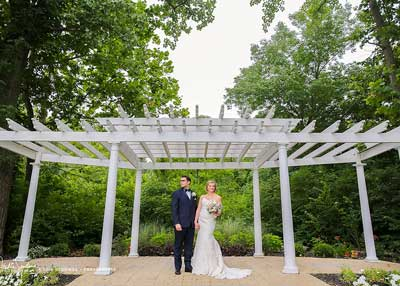 Bride and groom pose under the pergola at the outdoor wedding venue at The Lakefront Garden in Indianapolis