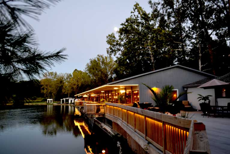Dusk at The Lodge at The Willows, a lakefront venue featuring a deck and fire pits
