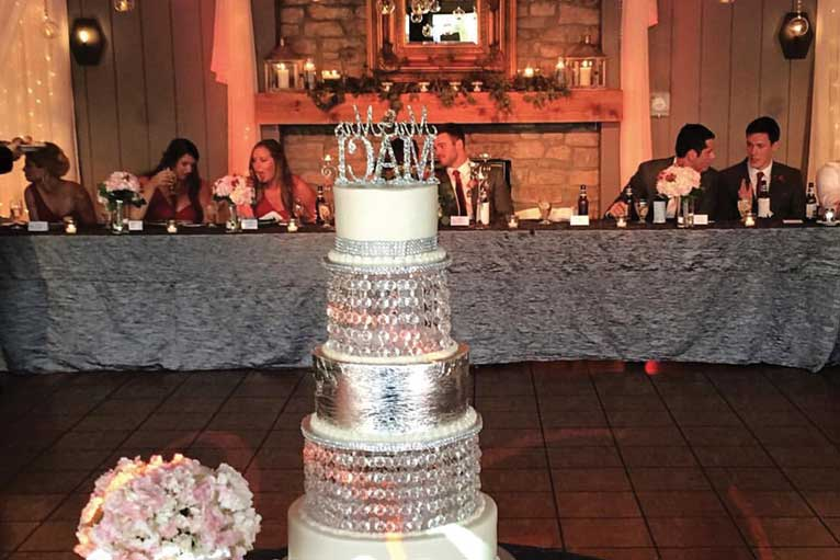 Wedding cake and head table at a glamorous wedding reception at The Lodge at The Willows