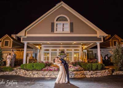 The newlyweds kiss in front of their Indianapolis wedding reception venue, The Ballroom at The Willows