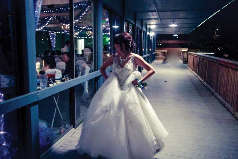 Bride poses on the terrace of the Indianapolis lakefront venue The Lodge at The Willows