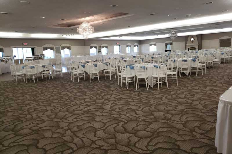 The Ballroom at The Willows with new carpet and white chairs for a formal event