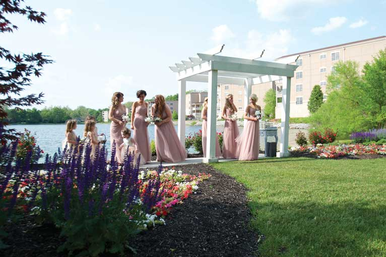 Bridesmaids dressed in pink wait to walk down the aisle at an outdoor wedding ceremony in Indianapolis at The Lakefront Garden